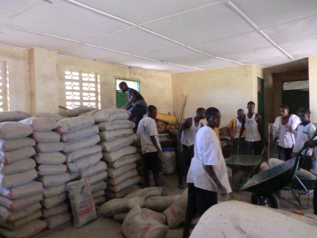 Zakken cement en gereedschap arriveren in het dorp